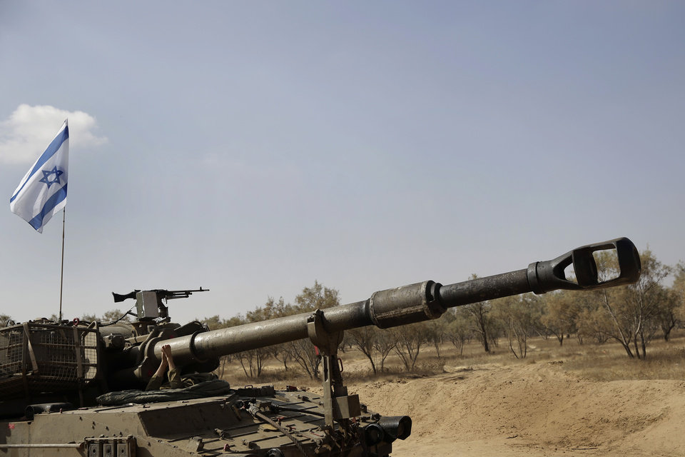 Photo - An Israeli soldier sleeps under the canon of a mobile artillery near the Israel and Gaza border, Sunday, July 27, 2014. Hamas on Sunday agreed to observe a 24-hour truce in Gaza after initially rejecting a similar Israeli offer, as fighting resumed and the two sides wrangled over the terms of a lull that international diplomats had hoped could be expanded into a more sustainable truce. Hamas spokesman Sami Abu Zuhri said the truce would go into effect at 2 p.m. (1100 GMT) Sunday. But shortly after the truce was to have started warning sirens wailed in southern Israel and the military said three rockets landed in the area, without causing casualties or damage. (AP Photo/Tsafrir Abayov)