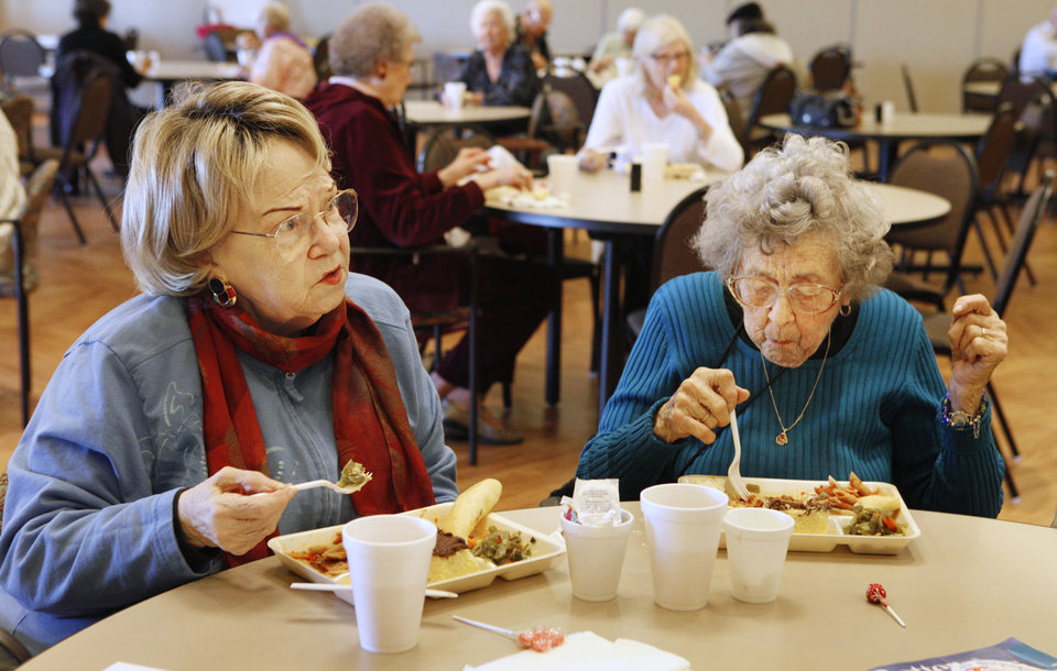 Photo - Verda Kenworthy and Mary Adams eat lunch at the Edmond Senior Center  in Mitch Park Tuesday. The meal program has been popular with Edmond seniors since it began.  PAUL B. SOUTHERLAND - PAUL B. SOUTHERLAND