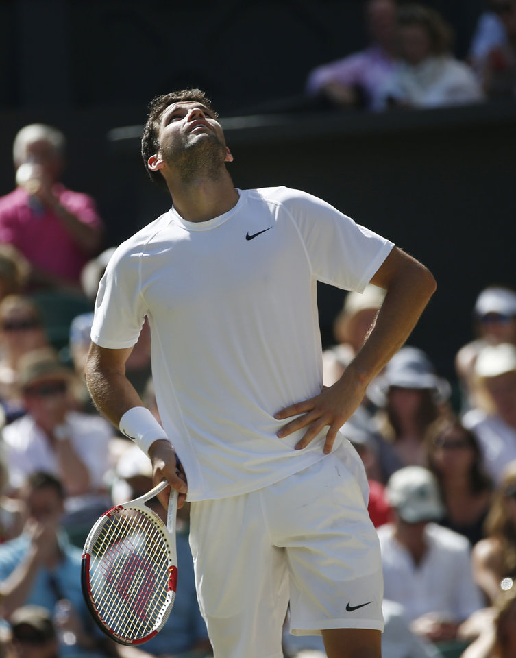 Photo - Grigor Dimitrov of Bulgaria looks up as he reacts to missing a point as he plays against Novak Djokovic of Serbia during their men's singles semifinal match at the All England Lawn Tennis Championships in Wimbledon, London, Friday, July 4, 2014. (AP Photo/Pavel Golovkin)