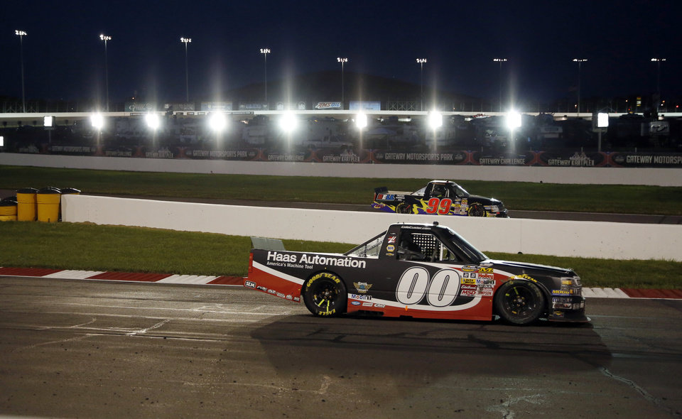 Photo - Cole Custer (00) exits Turn 4 as Bryan Silas (99) heads in for the pits during the NASCAR Truck Series auto race at Gateway Motorsports Park pn Saturday, June 14, 2014, in Madison, Ill. (AP Photo/Jeff Roberson)