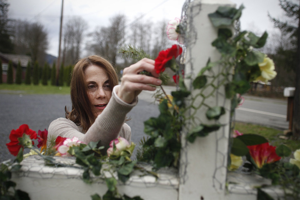 Photo - Tina Ray puts flowers on a cross in dedication of the mudslide victims at the Oso Community Chapel Wednesday, Mar. 26, 2014, in Oso, Wash. Tina and her husband, Pastor Gary Ray, run the Oso Community Chapel and are providing a place for victims and family members to come pray. (AP Photo/The Herald, Sofia Jaramillo)