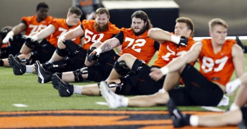Photo -  Oklahoma State football players stretch during the first spring football practice of the year on March 9 at the Sherman E. Smith Training Center in Stillwater. [Nate Billings/The Oklahoman]