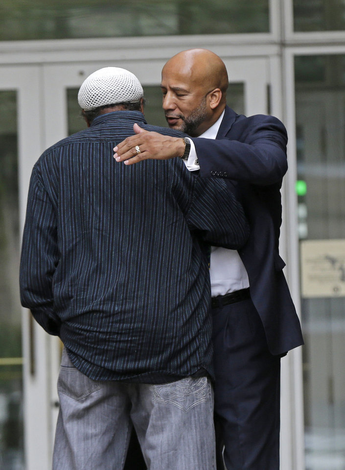 Photo - Former New Orleans Mayor Ray Nagin, right, hugs an unidentified person as he leaves federal court after being sentenced in New Orleans, Wednesday, July 9, 2014. Nagin was sentenced to 10 years in prison for bribery, money laundering and other corruption that spanned his two terms as mayor, including the chaotic years after Hurricane Katrina hit in 2005. (AP Photo/Gerald Herbert)
