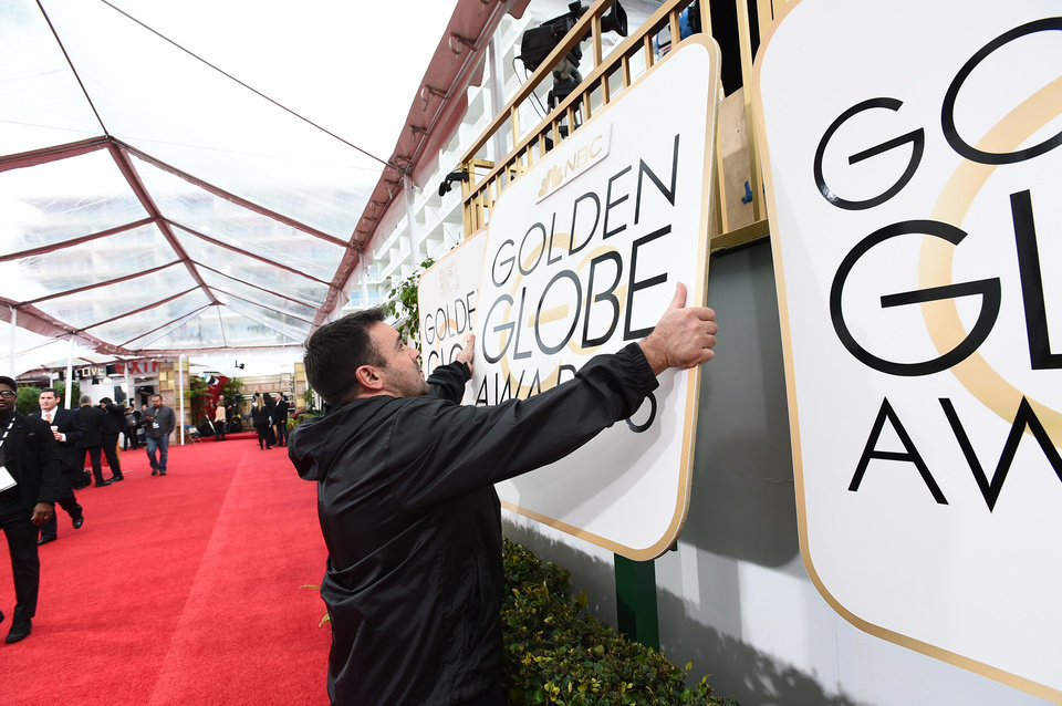 Photo - Workers prepare for the possibility of rain before the 72nd annual Golden Globe Awards at the Beverly Hilton Hotel, Sunday, Jan. 11, 2015, in Beverly Hills, Calif. (Photo by Jordan Strauss/Invision/AP)