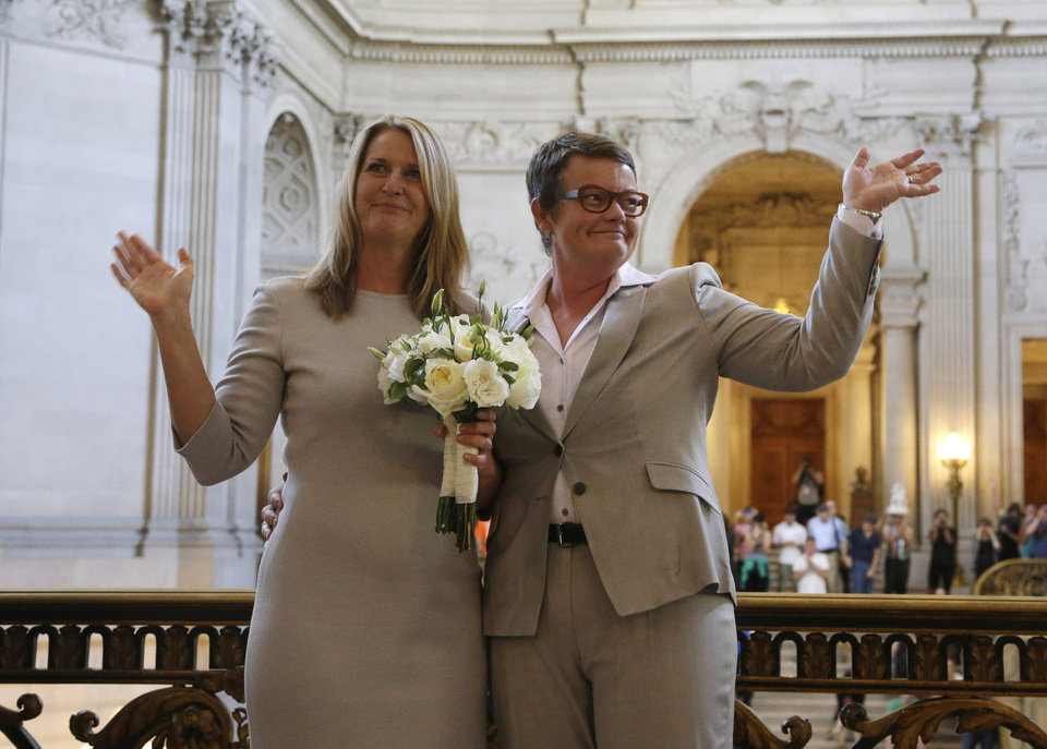 Photo - Sandy Stier, left, and Kris Perry wave at supporters after they were wed by California Attorney General Kamala Harris at City Hall in San Francisco, Friday,  June 28, 2013. Stier and Perry, the lead plaintiffs in the U.S. Supreme Court case that overturned California's same-sex marriage ban, tied the knot about an hour after a federal appeals court freed same-sex couples to obtain marriage licenses for the first time in 4 1/2 years. (AP Photo/Marcio Jose Sanchez)