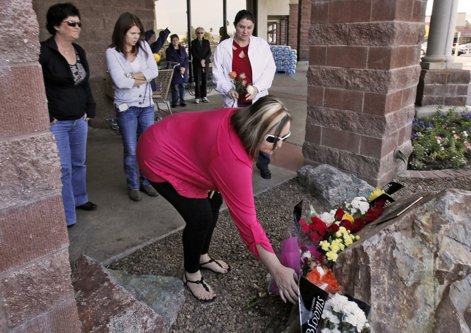 Photo - Melissa Shepherd, placing the flower, and staff members from a nearby office of Accounting Allies bring flowers to the memorial for the January 8, 2011, the Giffords shooting victims outside the Safeway store at Ina and Oracle Rd. north of Tucson, Ariz. on Wednesday, January 8, 2014. About a dozen people gathered spontaneously at the memorial where the shooting took place marking the third anniversary.    (AP Photo/Arizona Daily Star,Ron Medvescek )  ALL LOCAL TV OUT; PAC-12 OUT; MANDATORY CREDIT