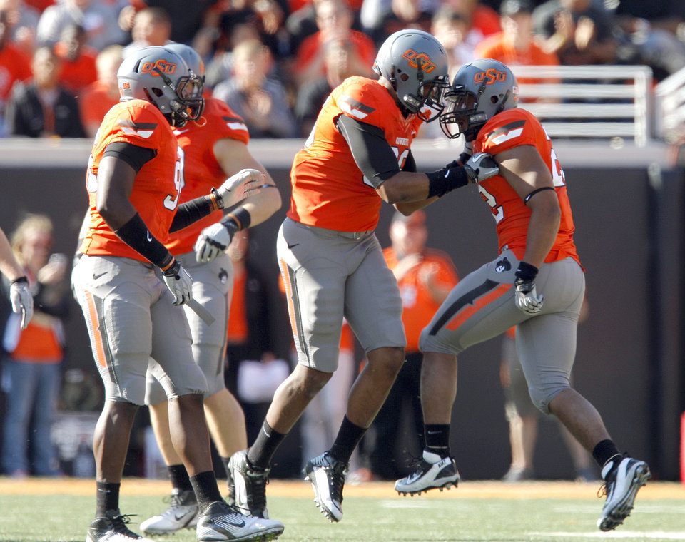 Photo - The Oklahoma State defense celebrates a play during a college football game between the Oklahoma State University Cowboys (OSU) and the Baylor University Bears (BU) at Boone Pickens Stadium in Stillwater, Okla., Saturday, Oct. 29, 2011. Photo by Sarah Phipps, The Oklahoman