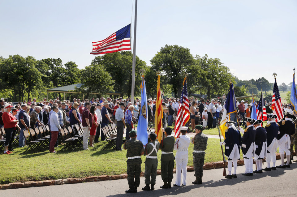Photo -  An American flag is lowered to half staff as it waves above the crowd during the 45th Infantry Division Museum's annual Memorial Day Ceremony on Monday. [Photo by Jim Beckel, The Oklahoman]