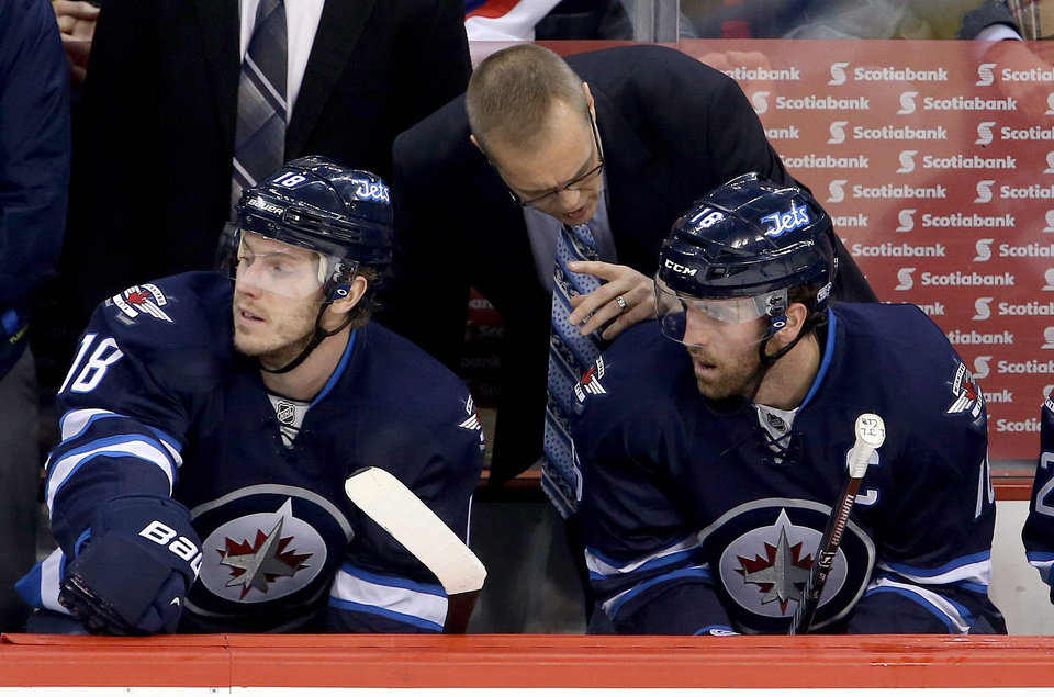 Photo - Winnipeg Jets head coach Paul Maurice talks with Bryan Little (18) and Andrew Ladd (16) during first period NHL hockey action against the Phoenix Coyotes in Winnipeg, Canada, Monday, Jan. 13, 2014. (AP Photo/The Canadian Press, Trevor Hagan)