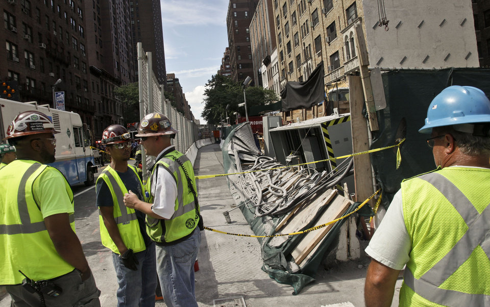 Workers examine damage following an intentional underground explosion on the Second Avenue subway project on East 72nd on Tuesday, Aug. 21, 2012. Blasting at the construction site for a New York City subway line has shattered windows and sent smoke billowing up to the street. Metropolitan Transportation Authority spokeswoman Marjorie Anders says something went wrong Tuesday as contractors were blasting a tunnel for the Second Avenue subway. She says no one was injured. (AP Photo/Bebeto Matthews)