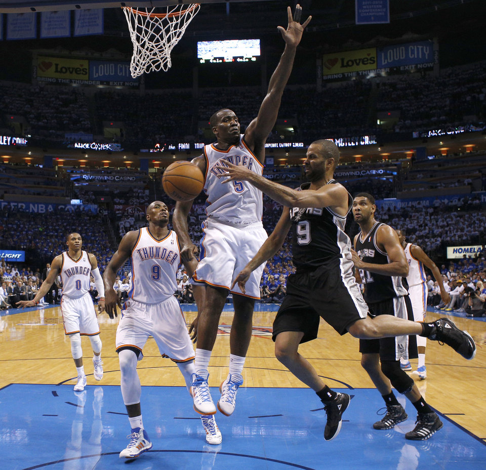 Photo - San Antonio's Tony Parker (9) passes the ball past Oklahoma City's Kendrick Perkins (5) and Serge Ibaka (9) during Game 4 of the Western Conference Finals in the NBA playoffs between the Oklahoma City Thunder and the San Antonio Spurs at Chesapeake Energy Arena in Oklahoma City, Tuesday, May 27, 2014. Photo by Bryan Terry, The Oklahoman