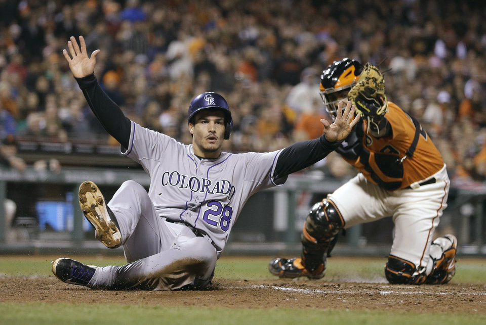 Photo - Colorado Rockies' Nolan Arenado, left, slides past San Francisco Giants catcher Hector Sanchez to score during the eighth inning of a baseball game Friday, April 11, 2014, in San Francisco. Arendo scored on a single by pinch-hitter Charlie Blackmon. (AP Photo/Eric Risberg)