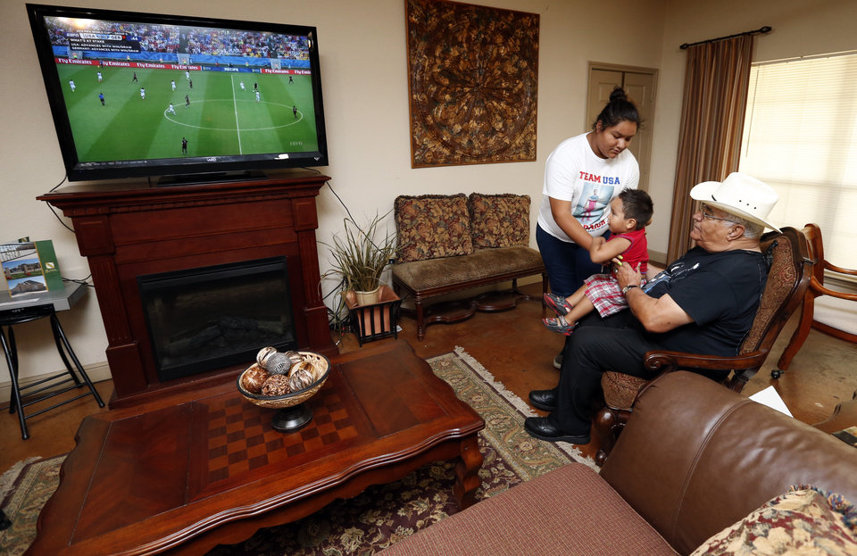 Photo -  Marla Cozad puts Zane Dupoint, 2, on grandpa Bill Elliott's lap as they watch another grandson, Chris Wondolowski, play against Germany for the American team in World Cup Soccer on Thursday in Lawton. Photo by Steve Sisney, The Oklahoman   STEVE SISNEY -  THE OKLAHOMAN