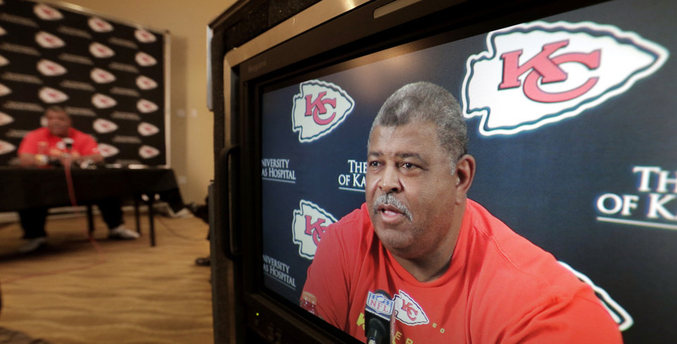 Photo - Kansas City Chiefs coach Romeno Crennel appears on a television monitor as he talks about linebacker Jovan Belcher during a news conference Monday, Dec. 3, 2012, at the NFL football team's practice facility in Kansas City, Mo. Crennel and Chiefs general manager Scott Pioli witnessed Belcher's suicide at the practice facility Saturday after, police said, Belcher shot and killed his girlfriend, Kasandra Perkins, at their Kansas City-area home. (AP Photo/Charlie Riedel)