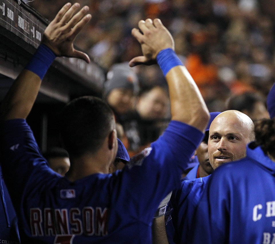 Photo - Chicago Cubs' Nate Schierholtz, right, is congratulated by Cody Ransom after hitting a solo home run off San Francisco Giants relief pitcher Sergio Romo in the ninth inning of a baseball game Saturday, July 27, 2013, in San Francisco. (AP Photo/Tony Avelar)