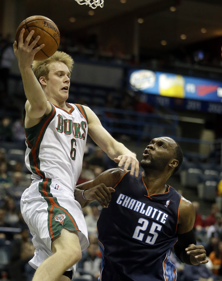Photo - Milwaukee Bucks' Nate Wolters, left, looks to pass over Charlotte Bobcats' Al Jefferson (25) during the second half of an NBA basketball game on Saturday, Nov. 23, 2013, in Milwaukee. (AP Photo/Morry Gash)