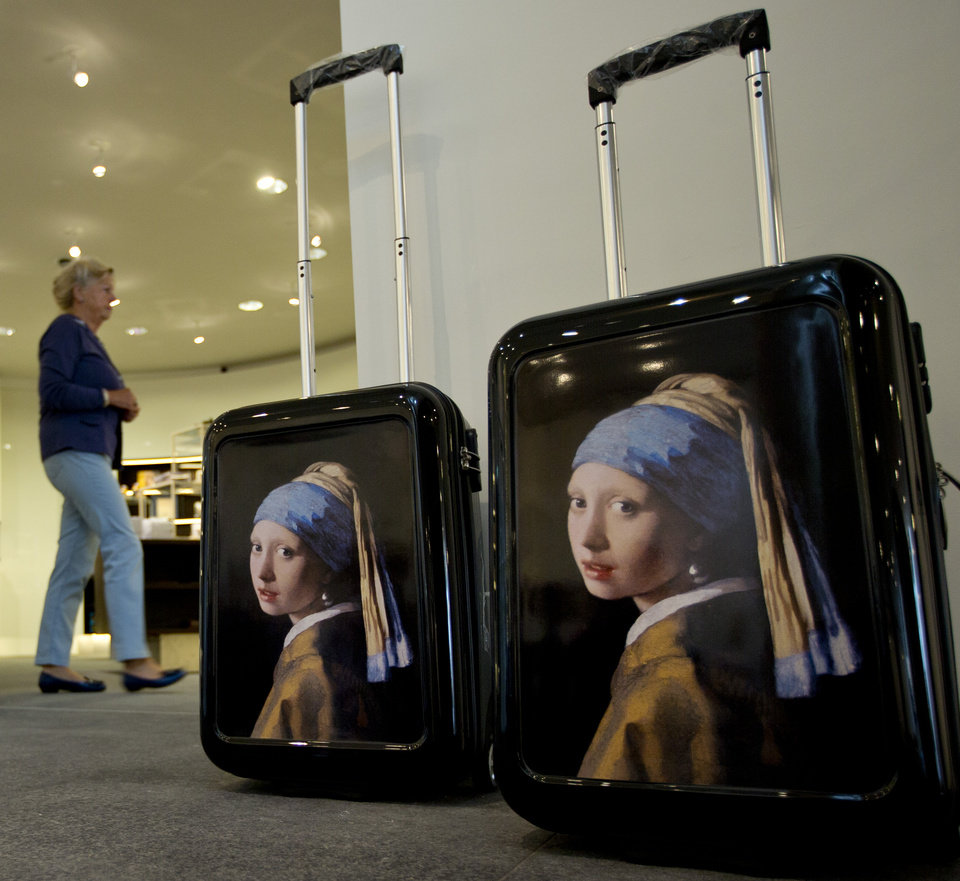 Photo - Suitcases with a reproduction of Johannes Vermeer's Girl with a Pearl Earring are on display at the souvenir shop during a preview for the press of the renovated Mauritshuis in The Hague, Netherlands, Friday, June 20, 2014. The Mauritshuis will open its doors to the public for free from 8 pm till midnight on Friday June 27th after the official ceremonial opening. From June 28 onwards the museum will revert to regular opening hours. (AP Photo/Peter Dejong)