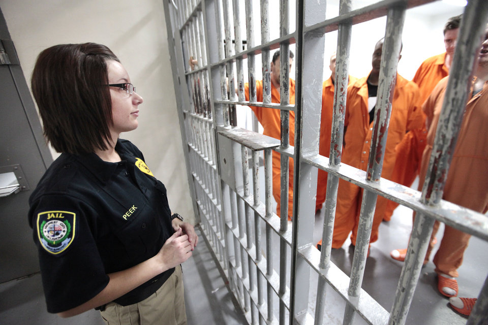 Photo - Midwest City jailer Jennifer Peek visits with inmates. Midwest City officials are working together with the state's mental health agency to start a new jail diversion program. It's similar to drug court or mental health court but on a city level.  David McDaniel - The Oklahoman