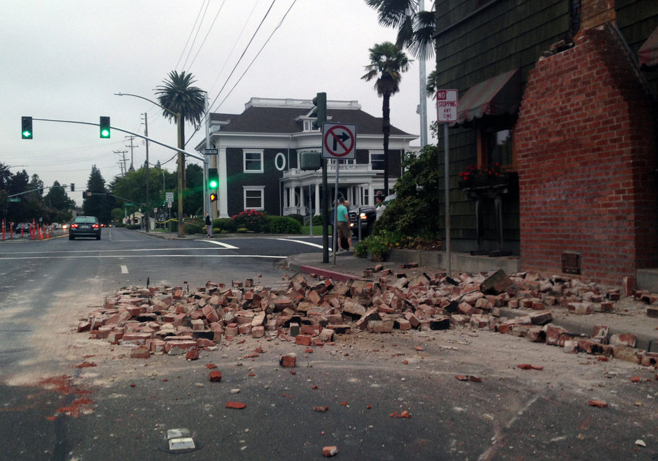 Photo - Bricks are in the street after a building was damaged during an earthquake in Napa, Calif., Sunday, Aug. 24, 2014. A large earthquake rolled through California's northern Bay Area early Sunday, damaging some buildings, knocking out power to thousands and sending residents running out of their homes in the darkness. (AP Photo/Ellen Knickmeyer)