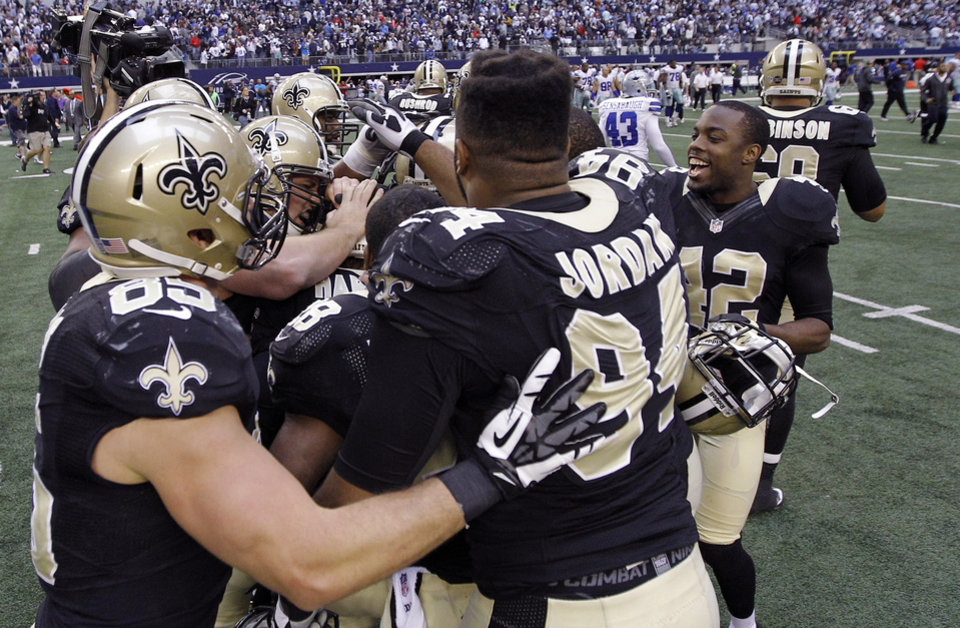 Photo - The New Orleans Saints celebrate at the end of overtime against the Dallas Cowboys at an NFL football game on Sunday, Dec. 23, 2012, in Arlington, Texas. The Saints won 34-31. (AP Photo/Brandon Wade)