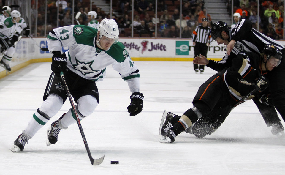 Photo - Dallas Stars right wing Valeri Nichushkin (43), of Russia controls the puck as Anaheim Ducks defenseman Hampus Lindholm, right, of Sweden collides into linesman Pierre Racicot in the first period of an NHL hockey game Saturday, Feb. 1, 2014, in Anaheim, Calif. (AP Photo/Alex Gallardo)