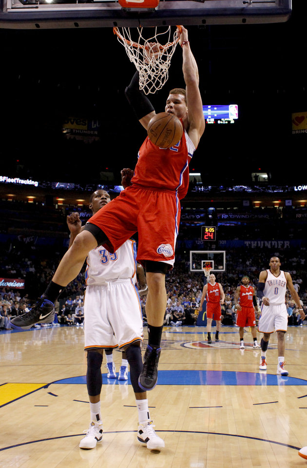 Photo - Los Angeles Clippers' Blake Griffin (32) dunks the ball in front of Oklahoma City's Kevin Durant (35) during the NBA basketball game between the Oklahoma City Thunder and the Los Angeles at the Oklahoma City Arena, Wednesday, April 6, 2011. Photo by Bryan Terry, The Oklahoman