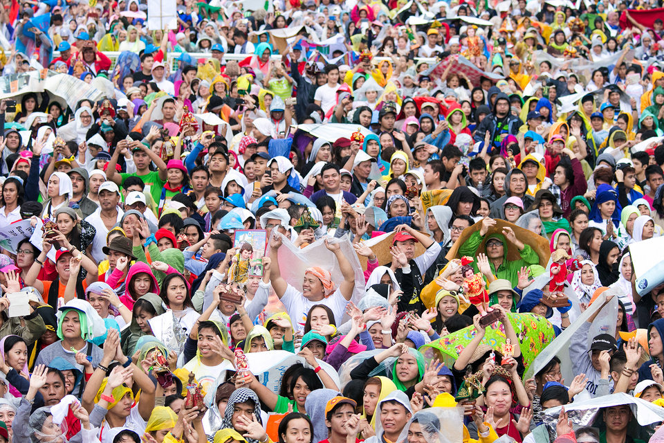 Photo - Filipinos raise their image of the Santo Nino (Holy Child) during the final papal mass of Pope Francis at Quirino Grandstand in Manila, Philippines, Sunday, Jan. 18, 2015. Millions filled Manila's main park and surrounding areas for Pope Francis' final Mass in the Philippines on Sunday, braving a steady rain to hear the pontiff's message of hope and consolation for the Southeast Asian country's most downtrodden and destitute. (AP Photo/Ron Soliman)