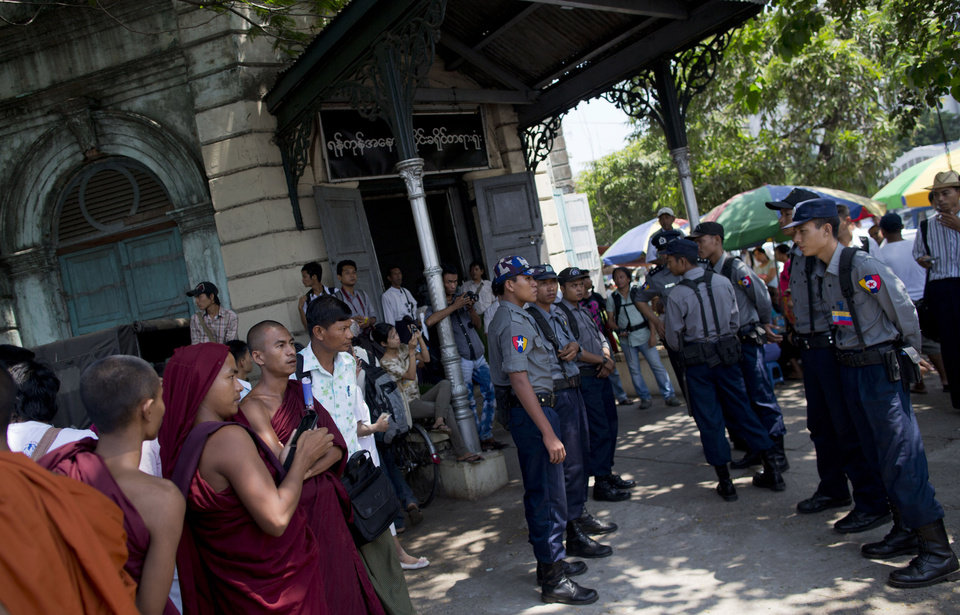 Photo - Police officers stand guard as monks, left, supporters of Ye Min Oo wait to see him at the district courthouse in Yangon, Myanmar on April 9, 2013. Plainclothes police seized the follower of the Buddhist monk, Wirathu, on the night of March 25, 2013 accusing him for inciting violence against Muslims and supporting extremist monks. (AP Photo/Gemunu Amarasinghe)