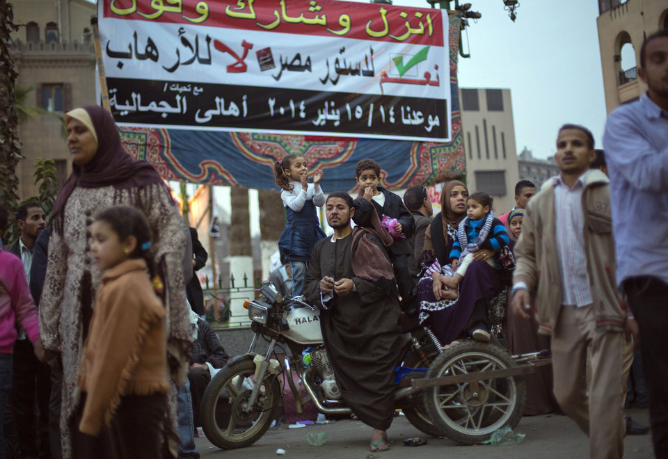 Photo - An Egyptian family sit on a motorbike under a banner with Arabic writing that reads,