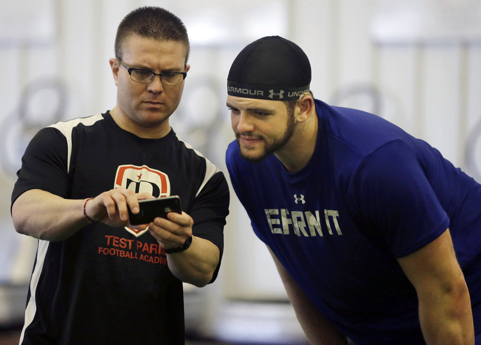 Photo - FILE - In this Friday, Feb. 14, 2014 file photo, Coach Kevin Dunn, left, goes over some techniques for the 40-yard-dash, between runs, with Gallaudet defensive lineman Adham Talaat, right, at his TEST Sports Clubs in Martinsville, N.J. Talaat has overcome being deaf to reach the doorstep of the NFL. After starring at Gallaudet University, working out at Test Parisi Football Academy and posted impressive numbers at his Pro Day, the talented defensive end is hopeful he'll get a call when the NFL draft kicks off next week. (AP Photo/Mel Evans,file)