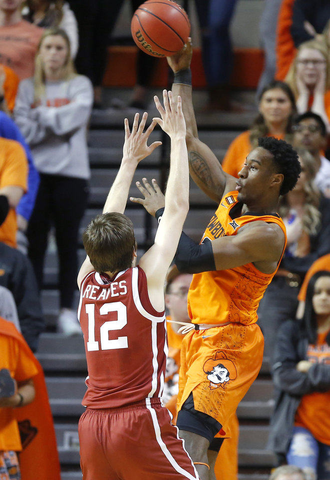 Photo - Oklahoma State's Cameron McGriff (12) passes the ball over Oklahoma's Austin Reaves (12) during an NCAA men's Bedlam basketball game between the Oklahoma State University Cowboys (OSU) and the University of Oklahoma Sooners (OU) at Gallagher-Iba Arena in Stillwater, Okla., Saturday, Feb. 22, 2020. Oklahoma State won 83-66. [Bryan Terry/The Oklahoman]