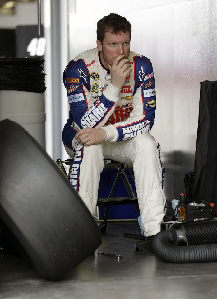 Photo - Dale Earnhardt Jr. waits in the garage before going out on the track during NASCAR auto race testing at Daytona International Speedway, Thursday, Jan. 10, 2013, in Daytona Beach, Fla. (AP Photo/John Raoux)