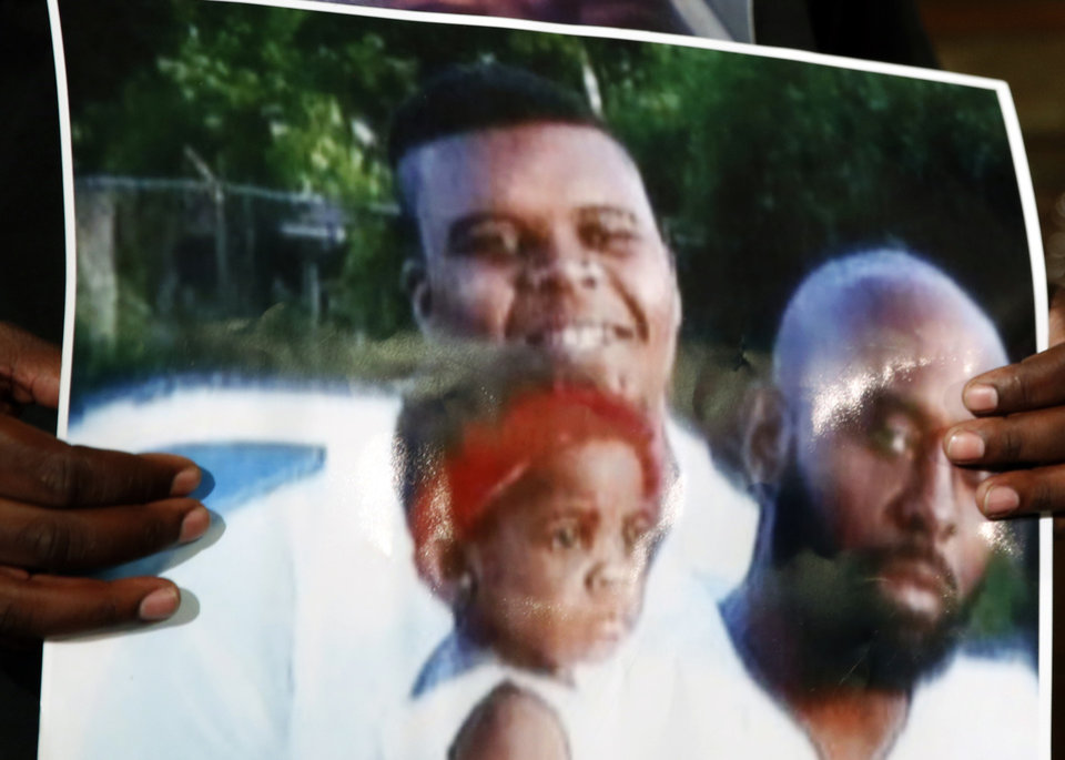 Photo - This undated family photo provided by the Brown Family and held by Michael Brown Sr., shows Michael Brown Sr., at right, his son, Michael Brown, top left, and a young child. Michael Brown, 18, was shot and killed in a confrontation with police in the St. Louis suburb of Ferguson, Mo, on Saturday, Aug. 9, 2014. (AP Photo/Jeff Roberson)