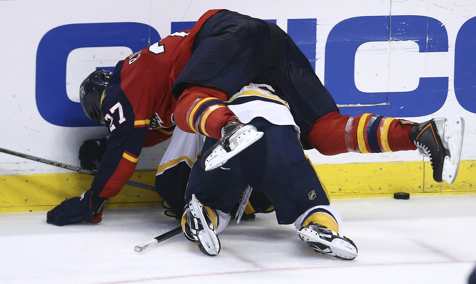 Photo - Florida Panthers' Nick Bjudstad (27) lands atop of Nashville Predators' Colin Wilson (33) as they fight for the puck during the third period of a NHL hockey game in Sunrise, Fla., Saturday, Jan. 4, 2014. The Panthers won 5-4 in an overtime shootout. (AP Photo/J Pat Carter)
