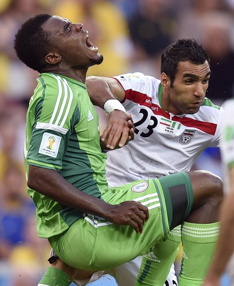 Photo - Nigeria's Emmanuel Emenike, left, grimaces after a challenge from Iran's Mehrdad Pouladi during the group F World Cup soccer match between Iran and Nigeria at the Arena da Baixada in Curitiba, Brazil, Monday, June 16, 2014.  (AP Photo/Martin Meissner)