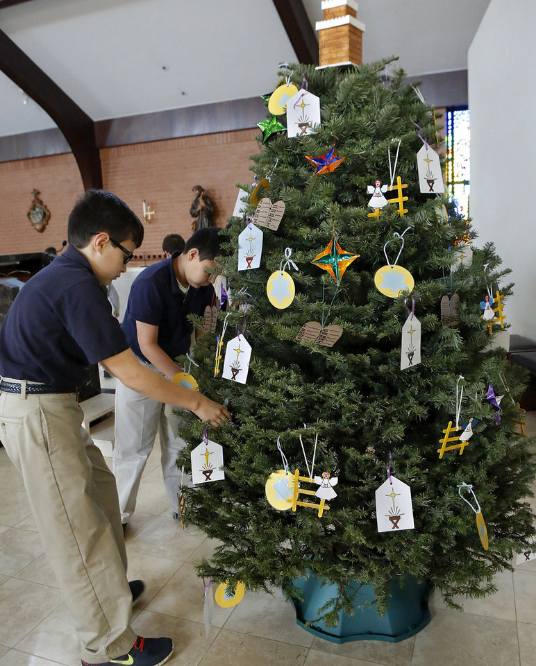 St. James Catholic School sixth grader Ben Krodel hangs ornaments on the Jesse Tree.