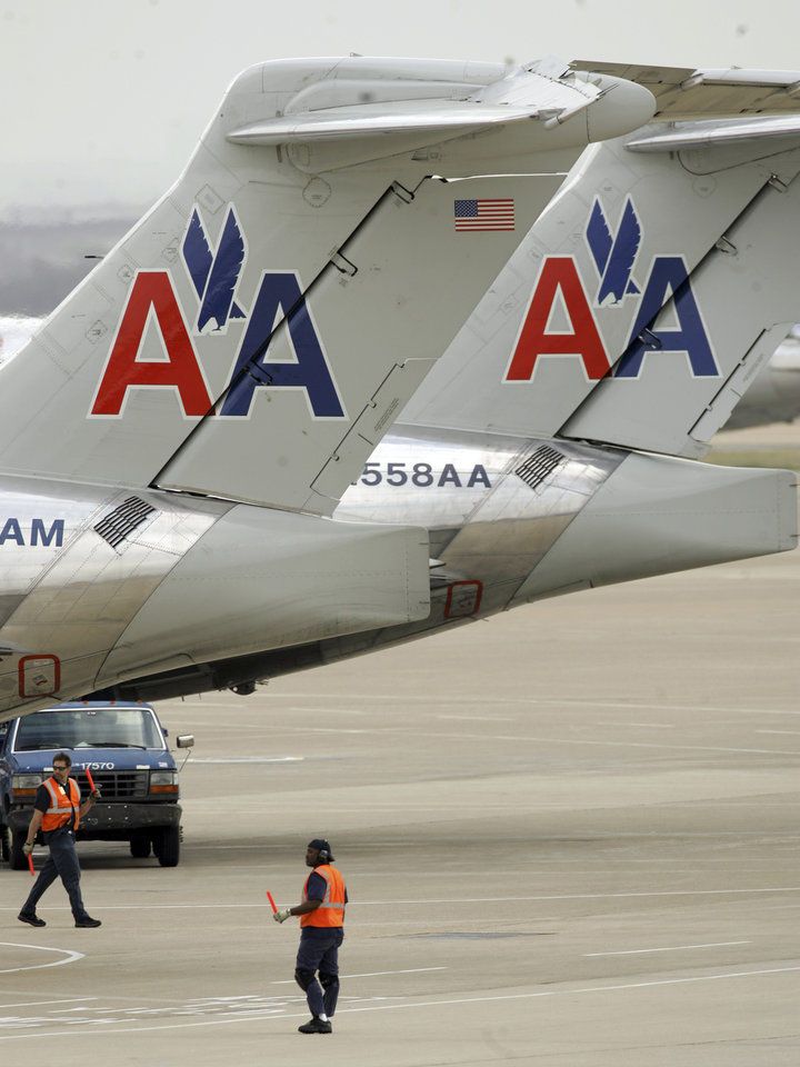 Photo - AIRPLANE, PLANE: Tail sections of two American Airlines MD-80 aircrafts sit above ground crew workers at Dallas Fort Worth international airport in Grapevine, Texas Wednesday, March 26, 2008. American Airlines canceled about 200 flights on so its crews can inspect some wire bundles aboard the MD-80 aircrafst.  The cancelled flights represent less than 10 percent of the nation's biggest airline's scheduled service for the day  (AP Photo/LM Otero) ORG XMIT: DN102