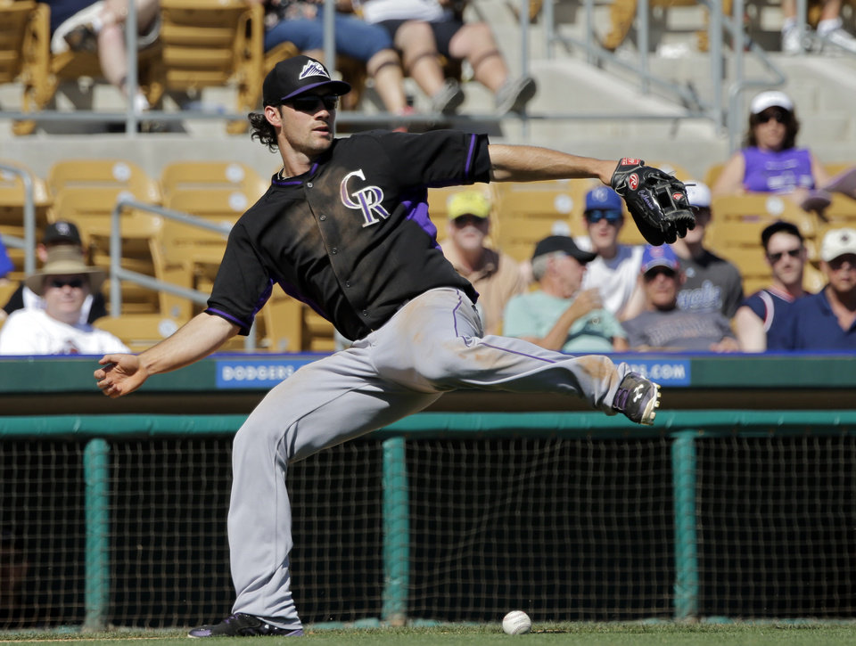 Photo - Colorado Rockies third baseman Charlie Culberson can't field a bunt by Chicago White Sox's Adam Eaton that went for a hit in the sixth inning of a spring exhibition baseball game Tuesday, March 25, 2014, in Glendale, Ariz. (AP Photo/Mark Duncan)