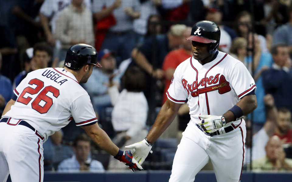 Photo - Atlanta Braves' Justin Upton, right, high-fives teammate Dan Uggla after hitting a home run in the second inning of a baseball game against the New York Mets, Thursday, April 10, 2014, in Atlanta. (AP Photo/David Goldman)