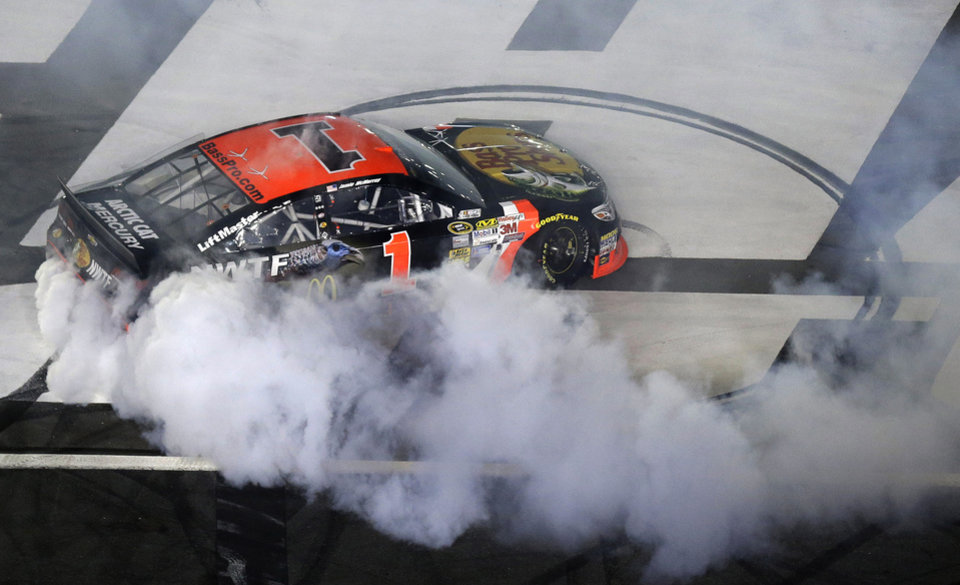 Photo - Jamie McMurray (1) does a burnout following his victory in the NASCAR Sprint All-Star auto race at Charlotte Motor Speedway in Concord, N.C., Saturday, May 17, 2014. (AP Photo/Gerry Broome)