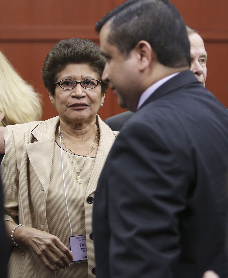 Photo - George Zimmerman's family, including Gladys Zimmerman, left, celebrate following George Zimmerman's not guilty verdict in Seminole Circuit Court in Sanford, Fla. on Saturday, July 13, 2013. Jurors found Zimmerman not guilty of second-degree murder in the fatal shooting of 17-year-old Trayvon Martin in Sanford, Fla. The six-member, all-woman jury deliberated for more than 15 hours over two days before reaching their decision Saturday night. (AP Photo/Gary W. Green, Pool) ORG XMIT: FLJR411