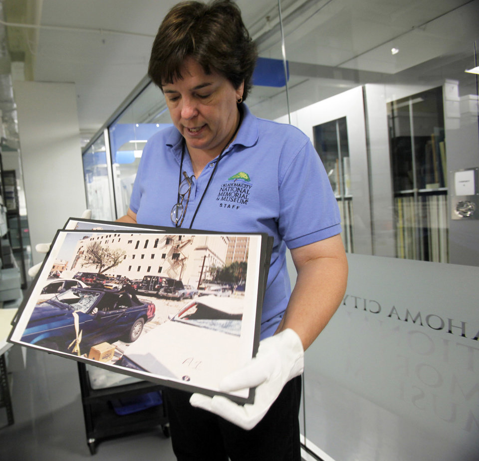 Helen Stiefmiller shows photos of the Murrah building after the bombing in the bombing museum's archives on Monday, July 1, 2013. Photo by Aliki Dyer/The Oklahoman