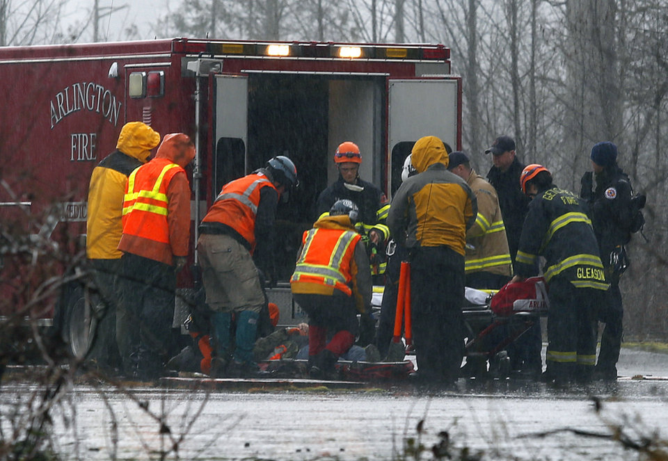 Photo - A helicopter and waiting ground crew transfer a worker injured working on the mudslide into a waiting ambulance from a Snohomish County helicopter, Tuesday, March 25, 2014, near Oso, Wash. A massive mudslide struck near Arlington, Wash., on Saturday, killing at least 14 people over the weekend and leaving scores more missing. (AP Photo/The Herald, Mark Mulligan)