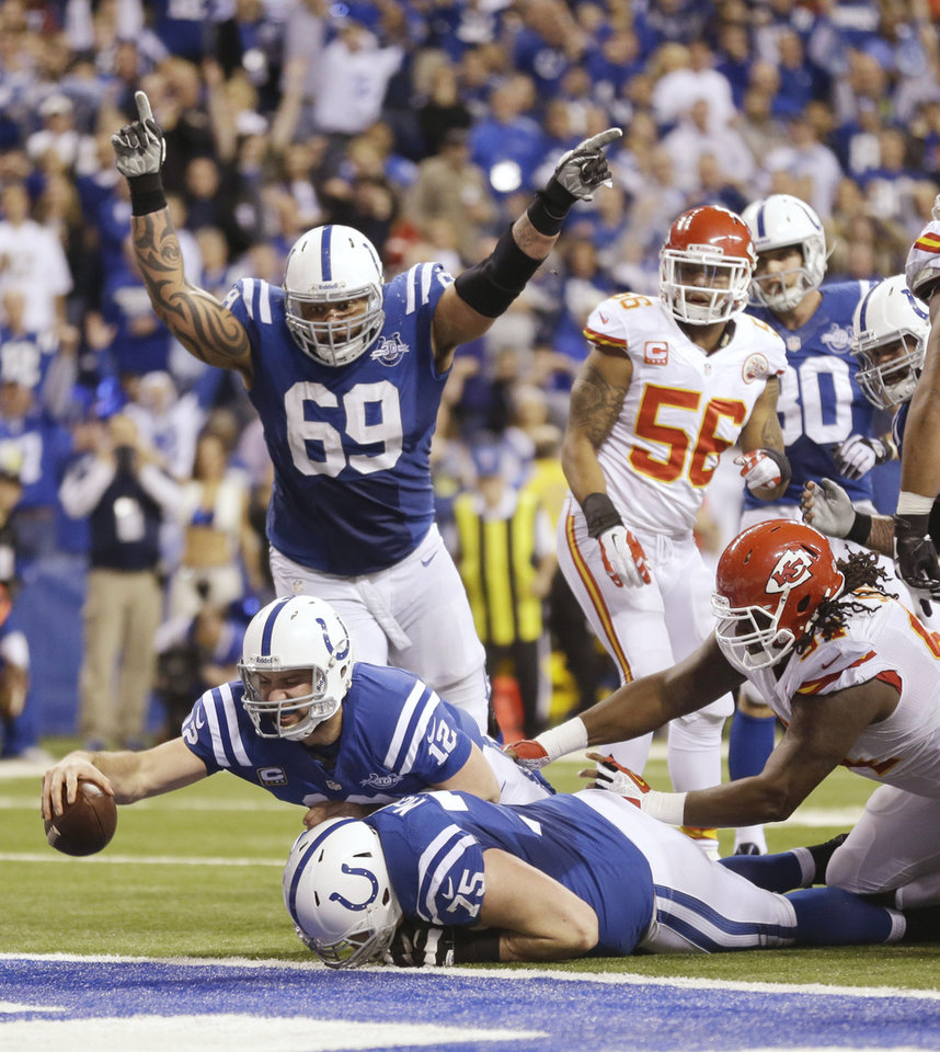 Photo - Indianapolis Colts quarterback Andrew Luck (12) dives for a touchdown after recovering a fumble by the Colts' Eric Berry during the second half of an NFL wild-card playoff football game against the Kansas City Chiefs Saturday, Jan. 4, 2014, in Indianapolis. (AP Photo/Michael Conroy)