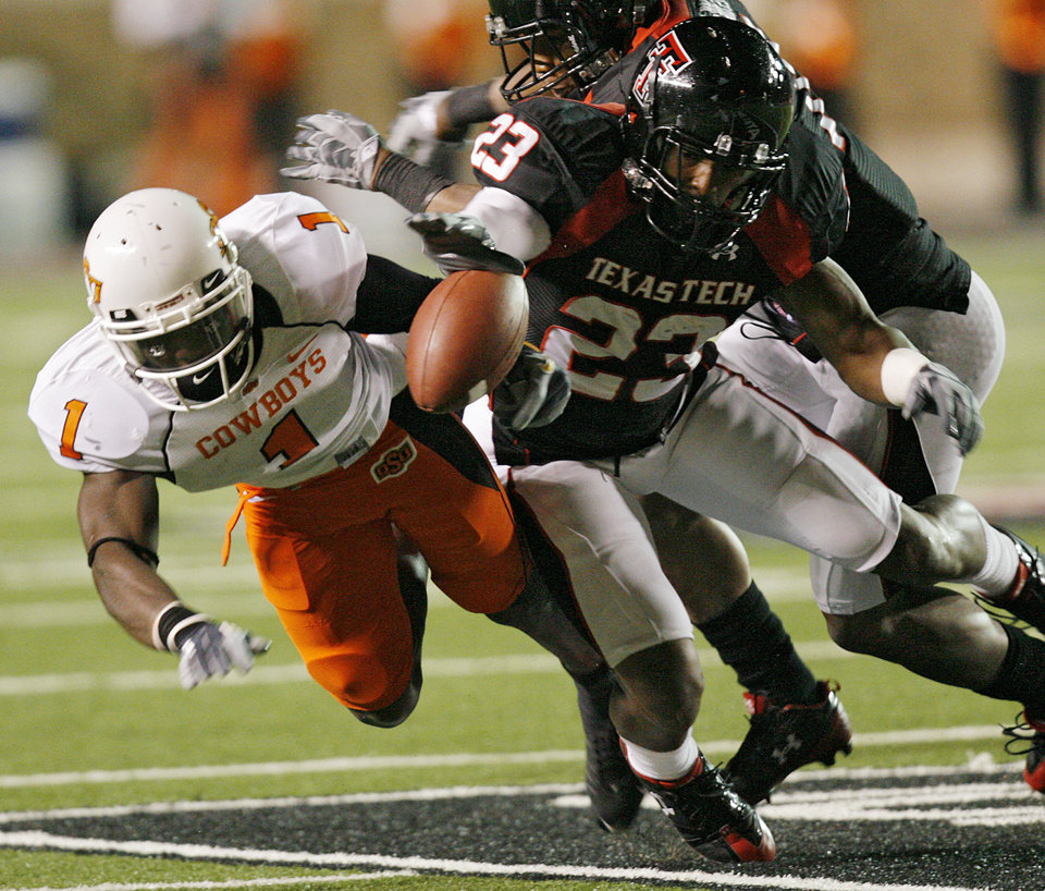 Photo - Texas Tech's Anthony Hines (23) breaks up a pass for Oklahoma State's Dez Bryant (1) during the first half of the college football game between the Oklahoma State University Cowboys (OSU) and the Texas Tech Red Raiders at Jones AT&T Stadium on Saturday, Nov. 8, 2008, in Lubbock, Tex.BY CHRIS LANDSBERGER/THE OKLAHOMAN