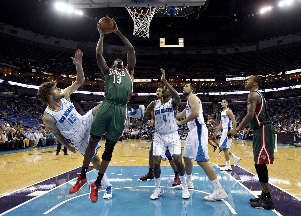 Milwaukee Bucks forward Ekpe Udoh (13) drives to the basket between New Orleans Hornets center Robin Lopez (15), forward Al-Farouq Aminu (0) and forward Ryan Anderson, right, in the first half of an NBA basketball game in New Orleans, Monday, Dec. 3, 2012. (AP Photo/Gerald Herbert)