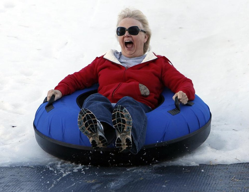 Linda Elliot, of Edmond, tubes down a snow slope at Chickasaw Bricktown Ballpark in Oklahoma City, Saturday, Nov. 24, 2012.  Photo by Garett Fisbeck, The Oklahoman