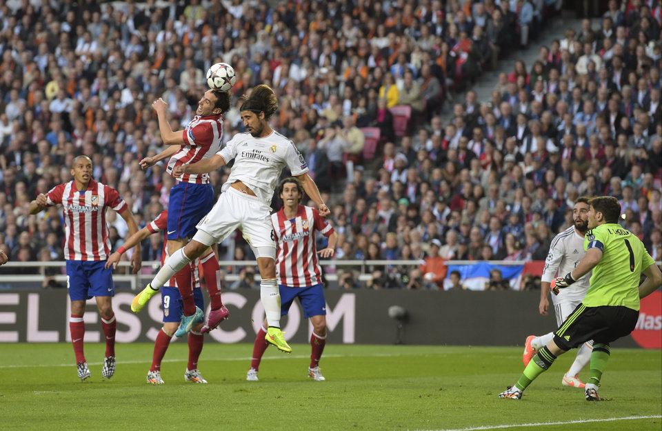 Photo - Atletico's Diego Godin, centre left scores the opening goal, during the Champions League final soccer match between Atletico Madrid and Real Madrid, at the Luz stadium, in Lisbon, Portugal, Saturday, May 24, 2014. (AP Photo/Manu Fernandez)