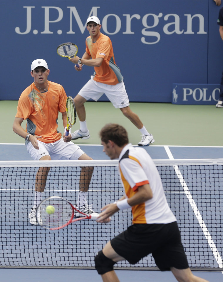 Photo -   Bob Bryan, left, and Mike Bryan, top, during men's doubles play against Nicolas Mahut and Julien Benneteau of France at the 2012 US Open tennis tournament, Wednesday, Sept. 5, 2012, in New York. (AP Photo/Mike Groll)