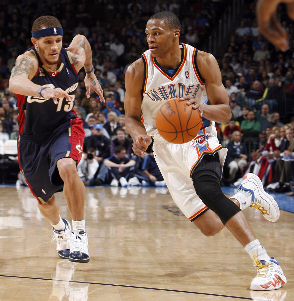 Photo - Oklahoma City's Russell Westbrook (0) drives to the basket as Cleveland's Delonte West (13) chases him during the NBA basketball game between the Oklahoma City Thunder and the Cleveland Cavaliers, Sunday, Dec. 13, 2009, at the Ford Center in Oklahoma City. Photo by Sarah Phipps, The Oklahoman ORG XMIT: KOD